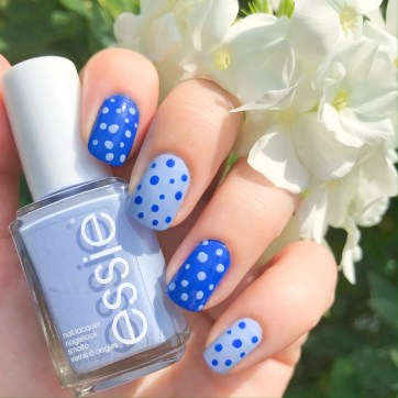 A hand holding a bottle of pastel blue essie nail varnish. The nails are painted alternately in light blue and bright blue polish. They have dots of the opposing colour polish painted on top.