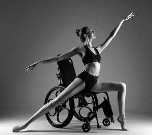 a black and white photograph of Kate dancing in her wheelchair in the arabesque positiontended, her other leg is bent at the knee