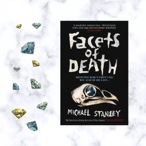 a copy of facets of death by Michael Stanley lying next to a handful of gem stones all set against a white marble background