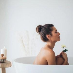 a woman sitting in a roll top bath