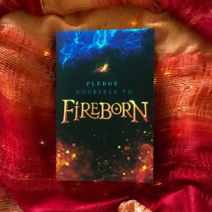 a copy of fireborn by aisling fowler lying on top of a flame colour scarf, beneath the scarf fairy lights can just be seen