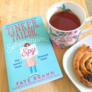 a copy of the paperback of tinker, tailor, schoolmum, spy on a wooden table with a cup of tea and a Danish pastry next to it.