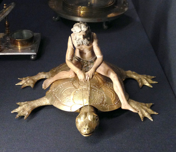 A man riding a little gold turtle!