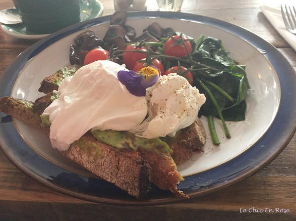 Breakfast of poached eggs, rye toast and wilted greens