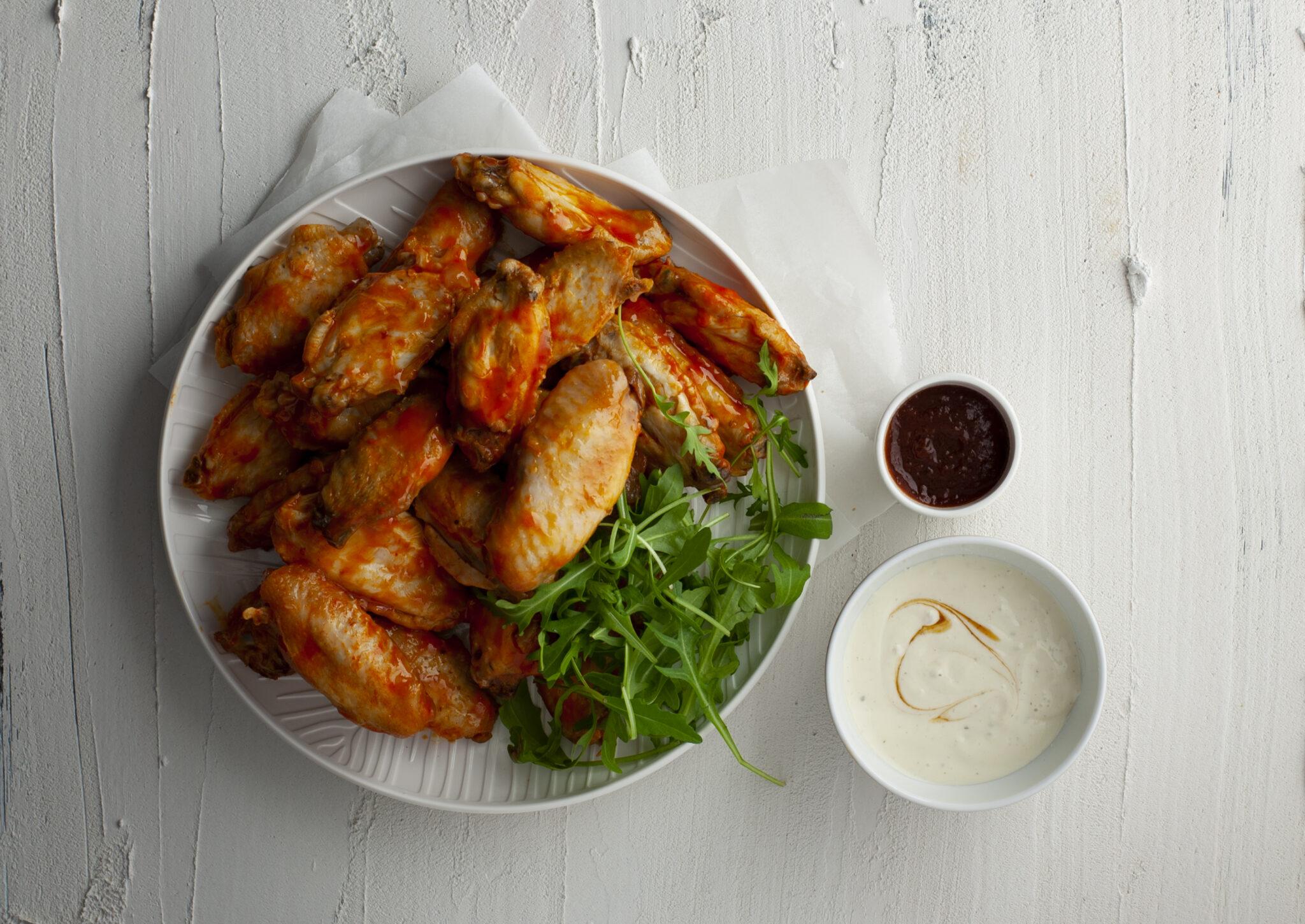 Bord chicken-wings op witte ondergrond