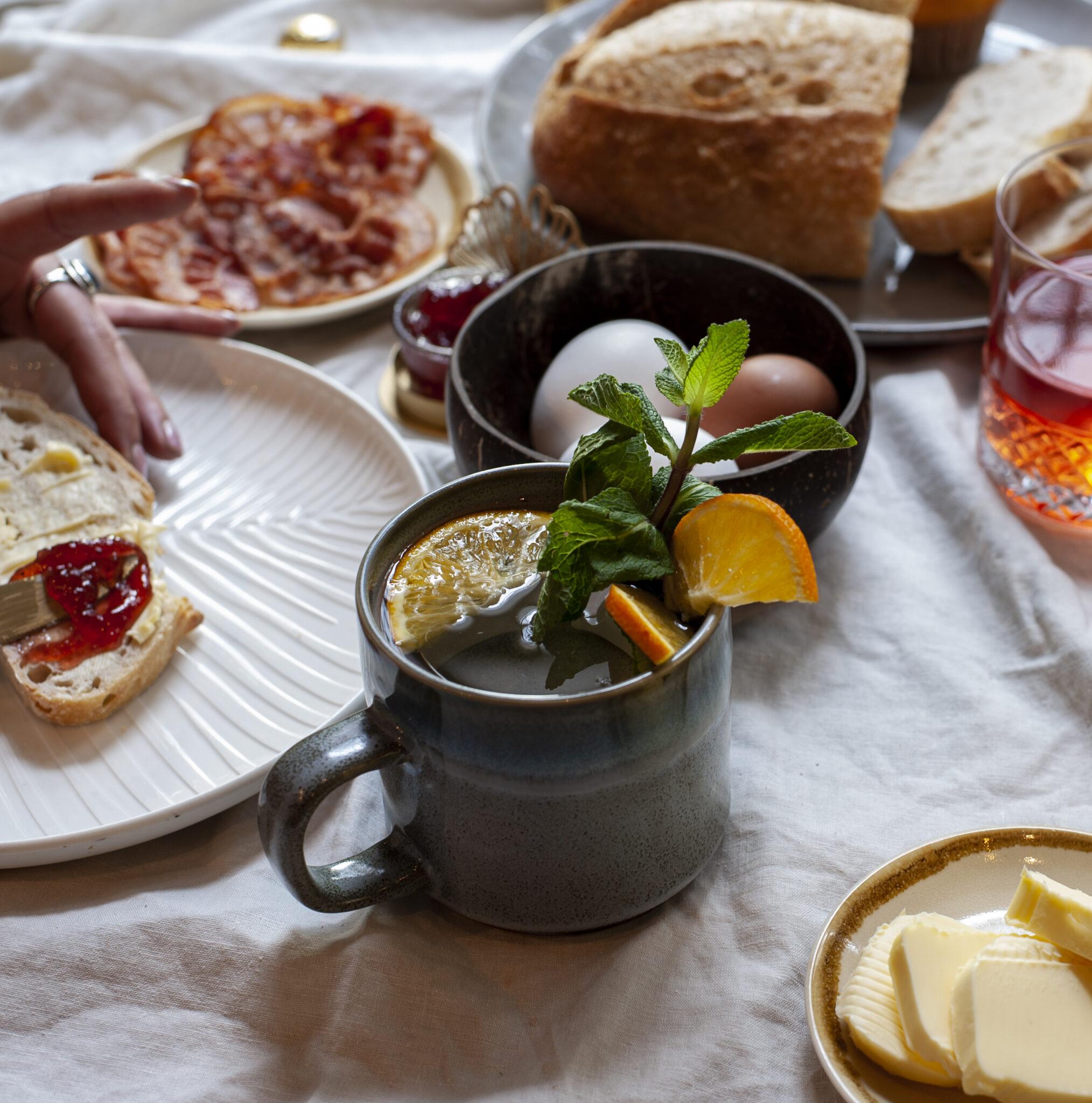 vrouw smeert boterham aan ontbijttafel