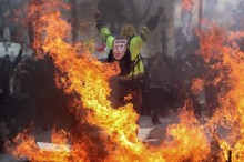 "A Yellow Vest protester wearing a mask depicting the French President on which is written 'psycho', gestures behind flames rising from barricades, in Paris on March 16, 2019, during the 18th consecutive Saturday of demonstrations called by the 'Yellow Vest' (gilets jaunes) movement. - Demonstrators hit French city streets again on March 16, for a 18th consecutive week of nationwide protest against the French President's policies and his top-down style of governing, high cost of living, government tax reforms and for more ""social and economic justice."" (Photo by Zakaria ABDELKAFI / AFP)"