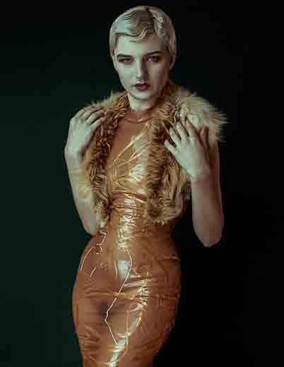 Woman with short blonde hair wearing a semi-transparent latex rust coloured dress with hand painted detailing.