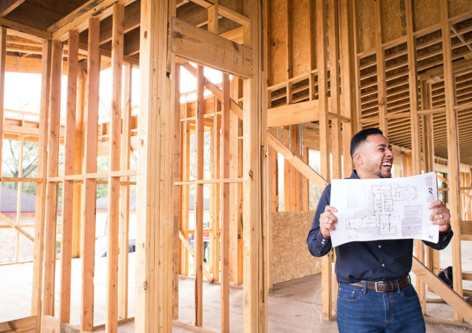 Contractor holding blueprint to camera while smiling