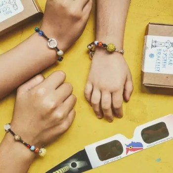 unique solar system bracelets featured on wrists with packaging
