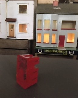 My red figure looking at the dolls house with the red door red on red