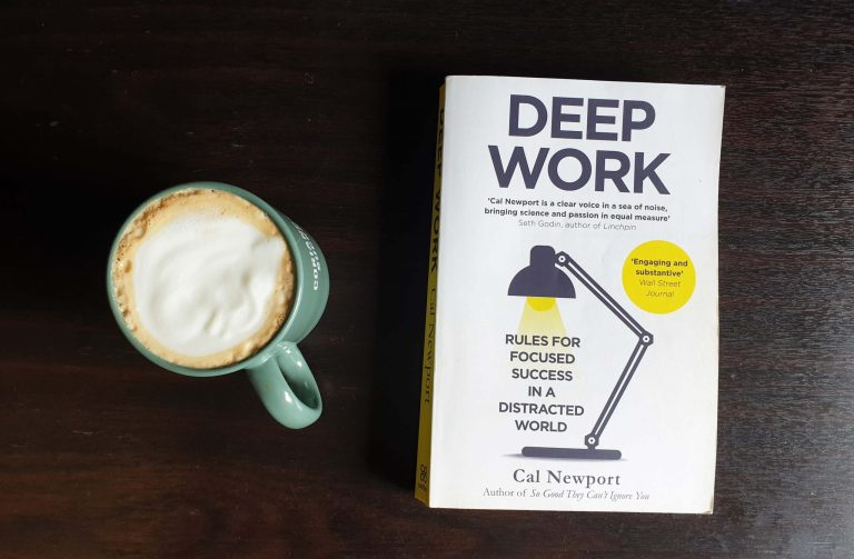 Deep Work Book By Cal Newport next to a mug of coffee