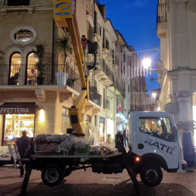 Workers hanging strings of Christmas lights on Piazza dei Signori - Vicenza, Italy - rossiwrites.com
