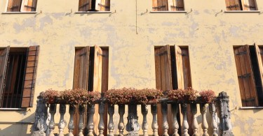 A peeling facade with a balcony and window shutters in Monselice, Colli Euganei, Italy