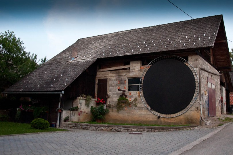 Kozolec - Traditional wooden hayrack barn with a huge trampoline leaning on it, Primostek, Slovenia - www.rossiwrites.com