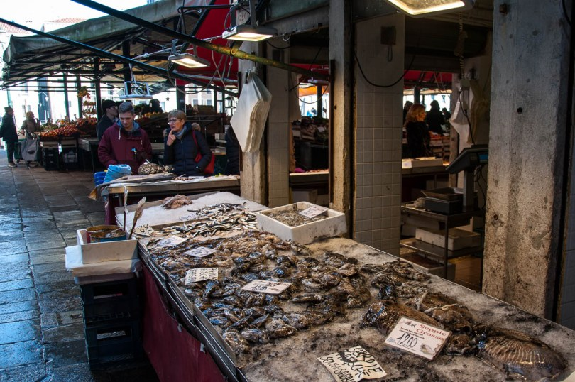 Customers looking at a fishmonger's stall - Rialto Fish Market, Venice, Italy - www.rossiwrites.com