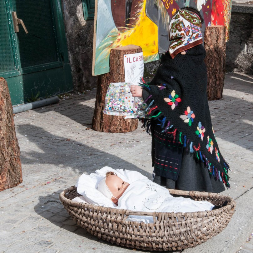 The baby doll and a girl in a traditional folk dress - Bagolino, Lombardy, Italy - www.rossiwrites.com