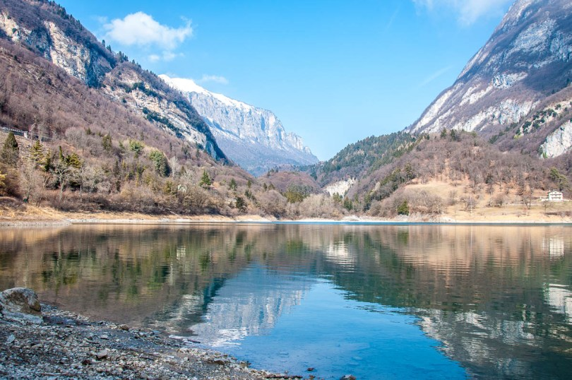 A view of lake Tenno surrounded by snow-capped mountain peaks - Trentino, Italy - rossiwrites.com