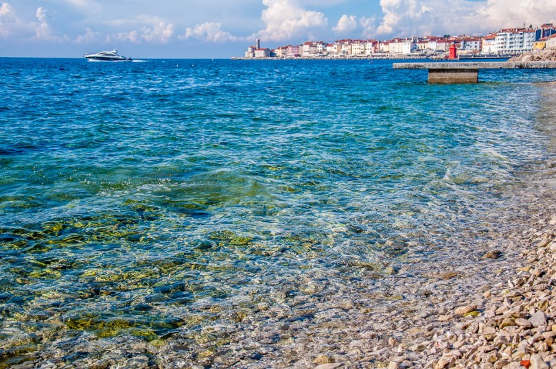 The crystal clear water of the Adriatic Sea with Punta Madonna in the background - Piran, Slovenia - www.rossiwrites.com