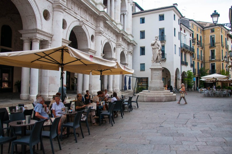 People having coffee in the shadow of the Palladio's Basilica and Palladio's statue - Vicenza, Veneto, Italy - rossiwrites.com