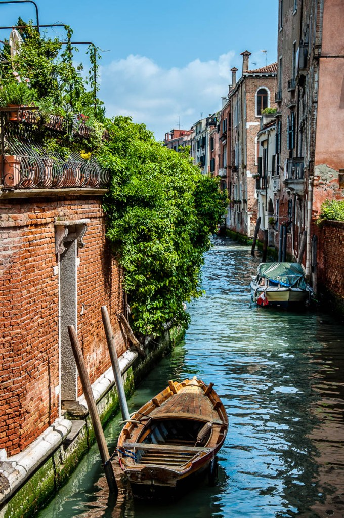 Venetian boat moored in a canal by a brick wall - Venice, Italy - rossiwrites.com