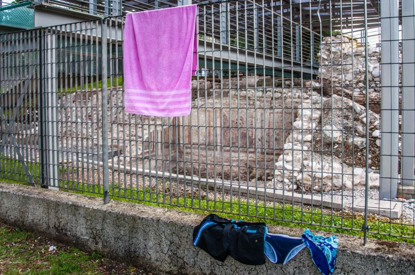 A towel and swimming costumes drying on the fence of the Ancient Roman villa - Bau Beach - Toscolano, Lombardy, Italy - rossiwrites.com