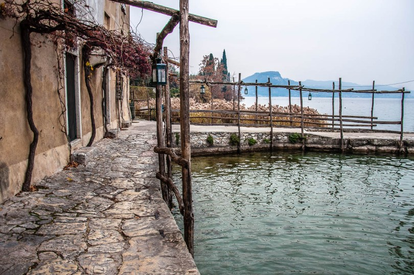 The stone path on the edge of the small harbour - Punta di San Vigilio - Lake Garda, Italy - rossiwrites.com