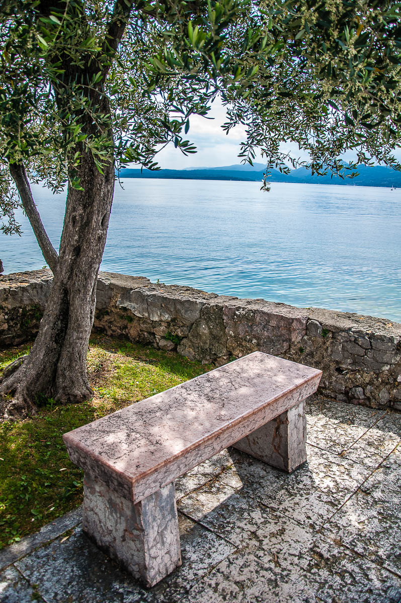 Bench on the edge of the historic harbour and overlooking Lake Garda - Torri del Benaco, Italy - rossiwrites.com
