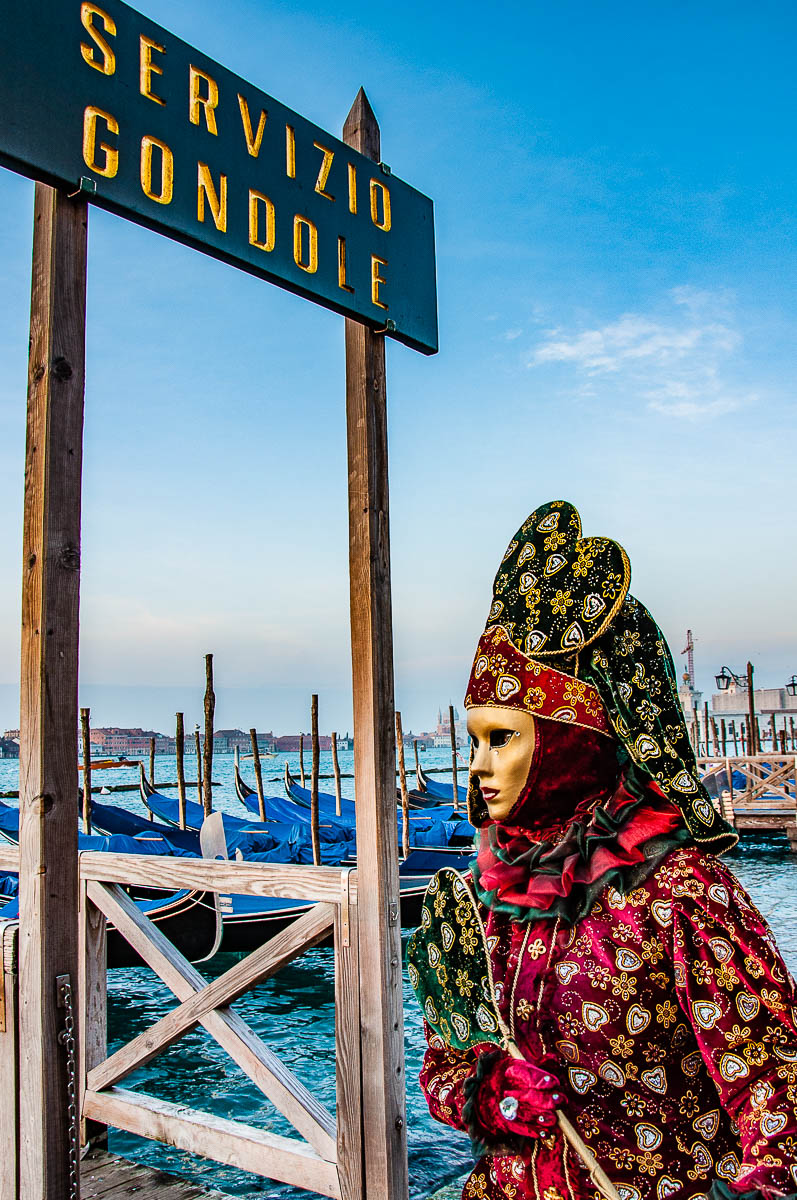 A beautiful Venetian mask standing next to the gondola service stand - Venice, Italy - rossiwrites.com