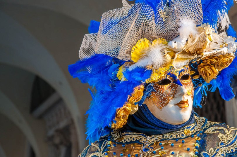 A beautiful mask in blue and gold in front of the Doge's Palace - Venice, Italy - rossiwrites.com