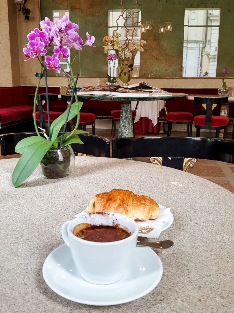 A Pedrocchi coffee served with a pastry on a table decorated with an orchid- Caffe Pedrocchi - Padua, Italy - rossiwrites.com
