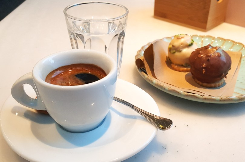 Espresso served with a glass of water and two chocolate sweets - Vicenza, Italy - rossiwrites.com
