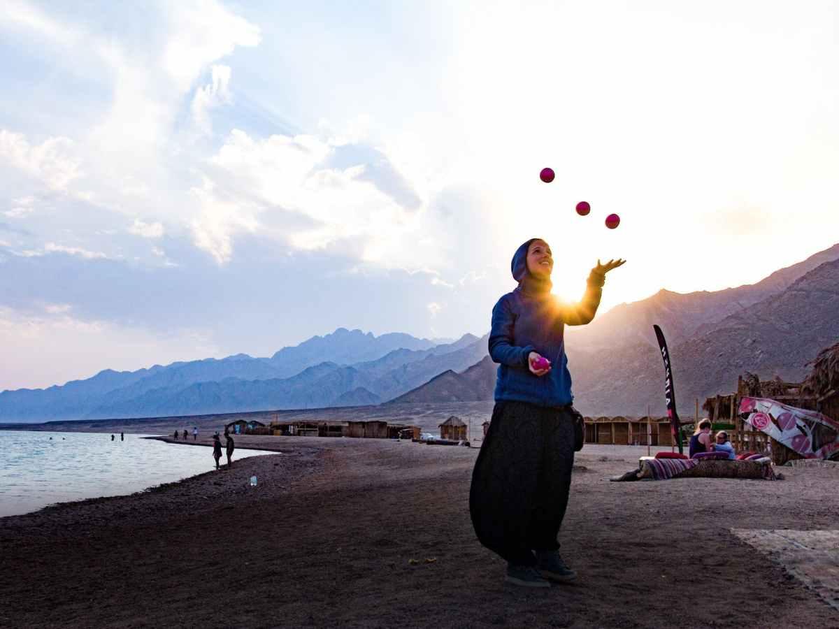 woman at the beach juggling