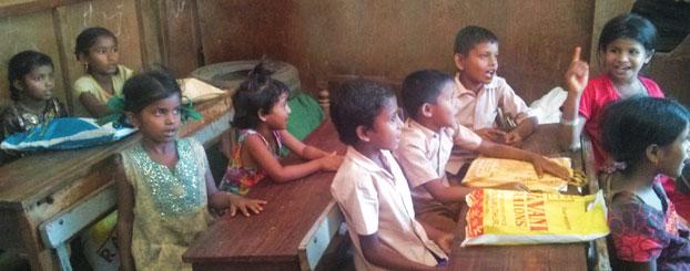 Assamese children reciting rhymes in school.