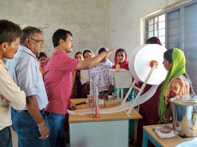 Micro-enterprise: Muruganantham giving out instructions to a few rural women about the machine.