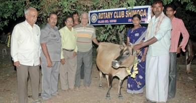PDG Narayan Pandeshwar (left) along with Rotarians gifting a cow to a beneficiary.