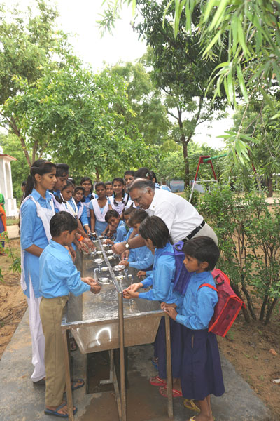 PDG Ramesh Agrawal encouraging the students to wash their hands.