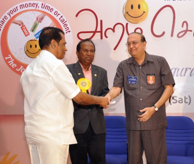 Rtn S.V. Balasubramaniam handing over cheque for Rs 5 lakhs to RI Director.