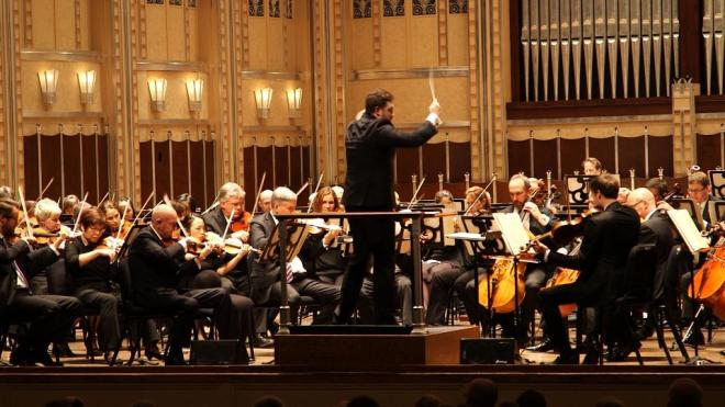 Associate Conductor Brett Mitchell leads The Cleveland Orchestra at the benefit concert in Severance Hall, which was completed in 1931 and has been called one of the world's most beautiful concert halls.