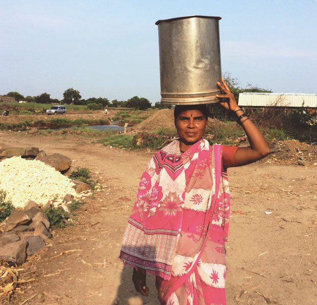 A woman carries water drawn from the hand-pump installed near the water-pits.