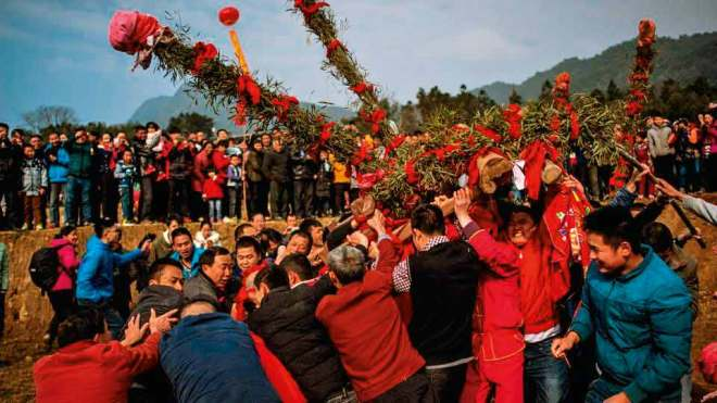 Beating the Buddha for good harvest In a unique ceremony leading up to the traditional Lantern Festival in February, Chinese villagers beat a rock-statue of the Buddha wishing for a good New Year and abundant harvest. The idol is wrapped in a red cloth and tied to a wooden palanquin. Four men attempt to carry it across a river, while another team tries to block them with freshly-hewn bamboo sticks. After a mock struggle, the defenders relent and the Buddha is welcomed into the village with fanfare. This tradition follows a legend where a village suffered heavy floods which ruined the harvest. One of the villagers dreamt of a Buddha idol buried in the fields that could stop the flooding. When they found it, the Buddha wanted to run away and people believed that beating the statue made Buddha stay on.