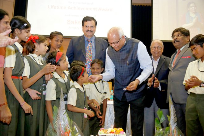 Eminent scientist Dr Raghunath Mashelkar with the children, flanked by AKS member Krishankumar B Jindal and DG Prashant Deshmukh on his left, and PDG Deepak Shikarpur on his right.