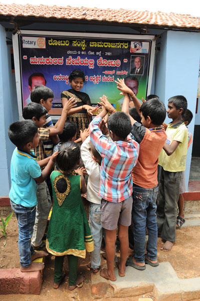 Suchitra demonstrates the hand-wash exercise to her schoolmates at her school. The banner behind is of RC Chamarajanagar, D 3181.