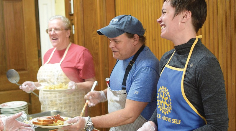 Kitchen Manager Bob Moses and Rotary Club member Emily Watts handed out lunches at the Berkshire Food Project on Tuesday. The nonprofit serves about 100 free lunches every weekday.