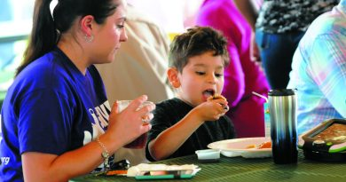 A mom watches her 5-year-old son chomp down on some flapjacks at the Rotary Club of Martinsburg's 8th Annual Pancakes for Polio breakfast.