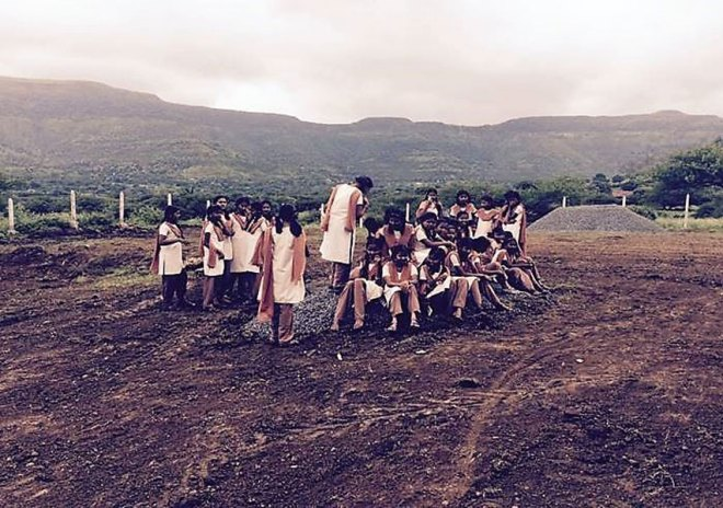 Before the school was built, students sat on heaps of stones.