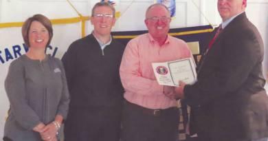 Troy Rotarians Melissa Kleptz, Patrick Titterington and club president Richard Bender accept the award from superintendent Eric Herman.