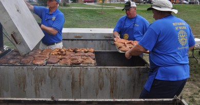 Volunteer cooks with the Rotary load ribs on the grill.  Photo: Jeffrey Cunningham