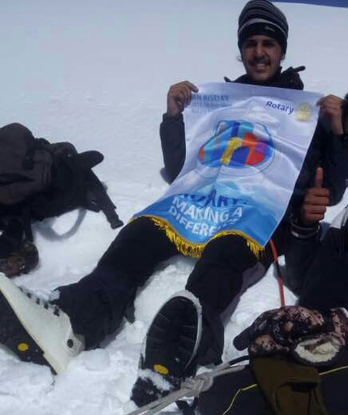 Kanwar Udey Singh Pannu with the Rotary theme banner on the Norbu peak.