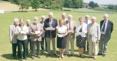 Members of the Rotary Club of Crediton, immediate past president Paul Evans centre front, with recipients of cheques holding their cheques with Sandford cricket field and Creedy Park behind them.